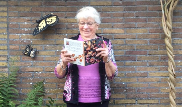 """Trots laat Janny de Veer zich fotograferen in haar tuin. Met haar eigen boekje: """"Mijn Hoogtijdag, overpeinzin-gen van Janny de Veer"""""""