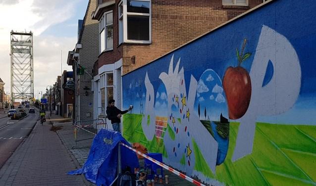 Het saaie hek tegenover het gemeentehuis wordt met graffiti opgeleukt en is fijn voor het oog. Wat gaat daar komen? Foto's: Debbie de Geus