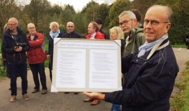 Bij een wandeling met Staatsbosbeheer door het Oosterpark heeft Jan Rijsdijk (rechts) een ingelijst overzicht voor wethouder Marten Japenga (in het midden met rood jack ) van 23 jaar wachten op een scherm. (Foto PR)