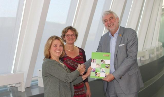 Atie Wakkee en Margret van Paassen overhandigen een pakket aan wethouder Peter Snoeren. (foto: gemeente Nieuwegein)