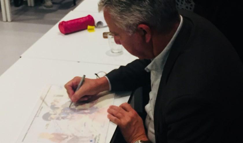 Wim Ludeke, voorzitter College van Bestuur De Onderwijsspecialisten, zet handtekening