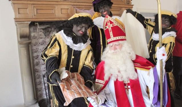 Tussen alle bezoekjes en drukke bezigheden door moet Sint-Nicolaas ook nog een nieuw behangetje kiezen om alle tekeningen van de kinderen op te plakken. De pieten hebben ideeën genoeg, maar Sint kan nog geen besluit nemen. (Foto: Lysette Verwegen)