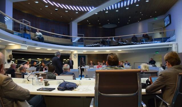 Een blik op de raadzaal van de gemeente Ede. Evert van Milligen (links, VVD) en Dirjanne van Drongelen (rechts, CU) staan voor het spreekgestoelte.