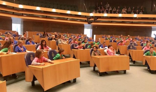 De kinderen mochten zitten in de blauwe zetels waar normaal de leden van Tweede Kamer zitten. foto: Julie Brugmans