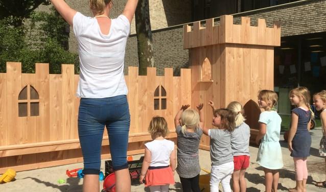 Kinderen op de peuterspeelplaats van de brede school De Sprankel in Haaren doen een spelletje met juffrouw Wendy.