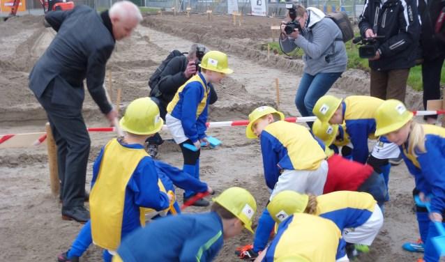 Onder grote belangstelling van (lokale) pers begonnen de jongste voetballertjes van Berghem Sport, uiteraard in het blauw/geel, met de bouw van het nieuwe clubhuis. Daarmee komt na 4 jaar voorbereiding een nieuw clubhuis voor de voetbalclub steeds dichterbij. Foto: Han Jansen
