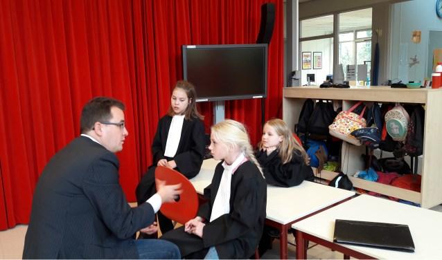 Drie rechters van de Prinsenakker bespreken hun zaak met een van de advocaten van de Junior Jurist Academie.