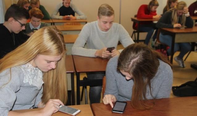 Via hun mobiele telefoons vullen de leerlingen van het CSG het Noordik een enquête in met allerlei uiteenlopende vragen over het Twentse dialect