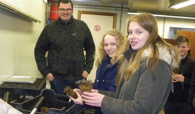 Manon (rechts) en Anne krijgen uitleg van Michel van der Werf over het winterklaar maken van plantgoed. Ze kregen een rondleiding bij de kennismaking bij drie Boskoopse boomkwekerijen. FOTO: Morvenna Goudkade