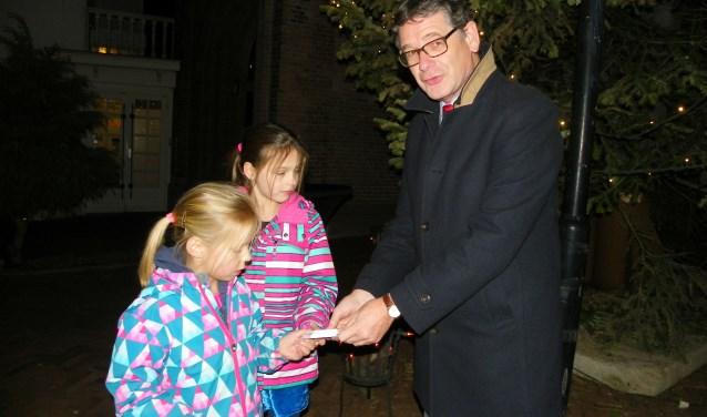 Wethouder Kees van Velzen ontsteekt de verlichting van de kerstboom, geholpen de zusjes Emma (li) en Lenthe. (Foto: Morvenna Goudkade)