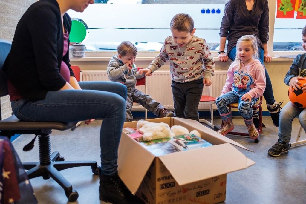 De kinderen van KC De Speeldoos in Zutphen pakken enthousiast hun Kinderkerstpakket uit.  Foto: www.Goodwill.nl  © Persgroep