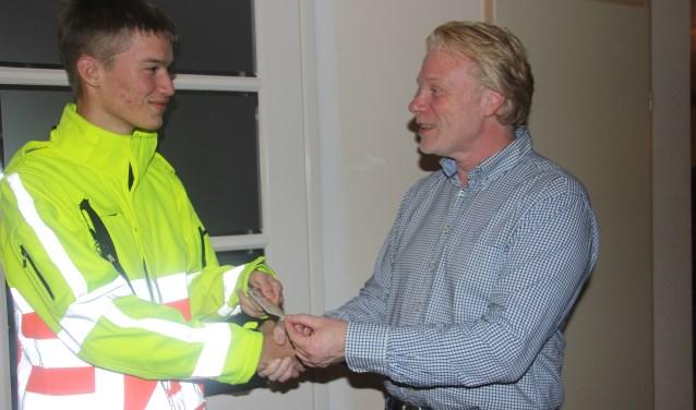 Pepijn (links) ontvangt uit handen van Robert Fuhrer de pas waarmee hij bevoegd is om zelfstandig bij evenementen of calamiteiten het verkeer te regelen