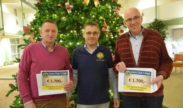 Voorzitters Rob de Jong (l) en Sjaak Berends (r) van de Zonnebloem Oudewater en Montfoort/Linschoten kregen uit handen van Onno Cleijpool van Lions Club Het Stigt ieder een welkome cheque overhandigd. (Foto: Paul van den Dungen)