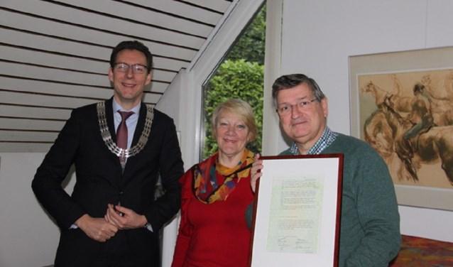 Mies en Adriaan tonen de kopie van de oorspronkelijke trouwakte die ze uit handen van Burgemeester Poppens mochten ontvangen.