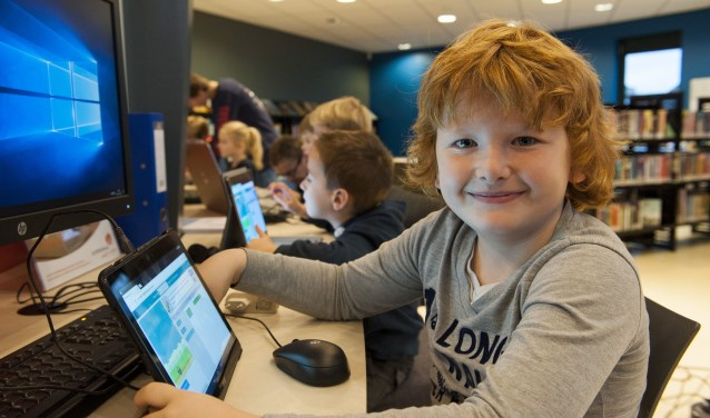 Joshua Vleeming leert in de bibliotheek hoe hij kan programmeren. De kinderen die aan het programma Flappy Bird meedoen, steken er heel wat van op. (foto: Ellen Koelewijn)