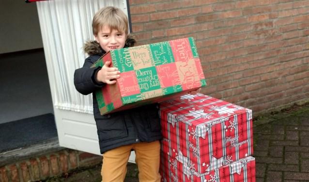 Julian (6 jaar) bezorgt samen met zijn moeder kerstpakketten.