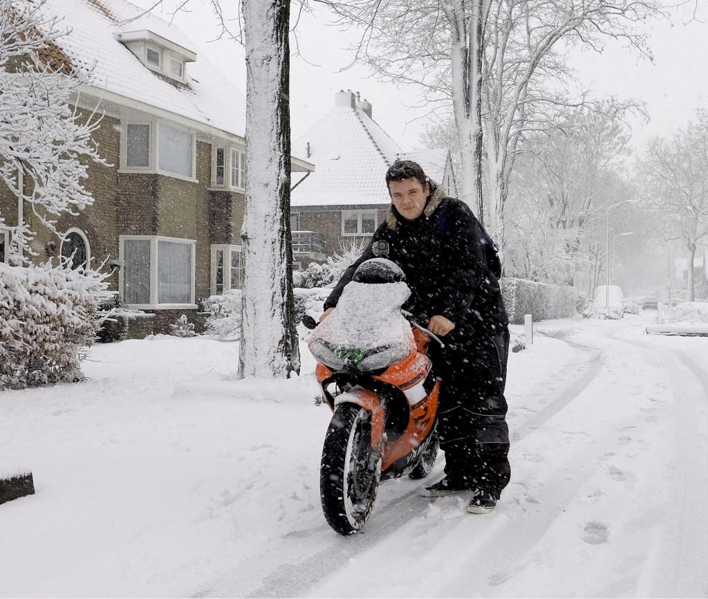 Zonder benzine kom je nergens met een bromfiets, dus werd het duwen voor Joris, in de sneeuw.  © Persgroep
