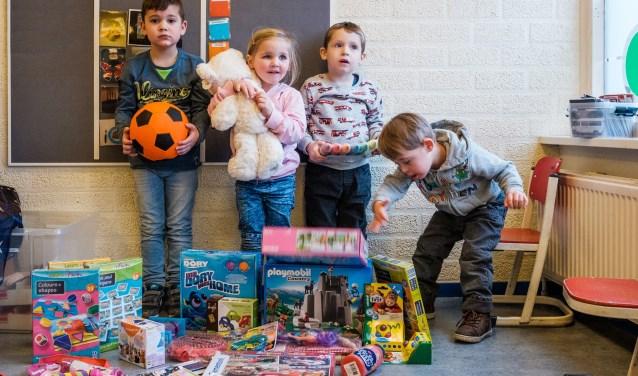 De kinderen van KC De Speeldoos in Zutphen pakken enthousiast hun Kinderkerstpakket uit.