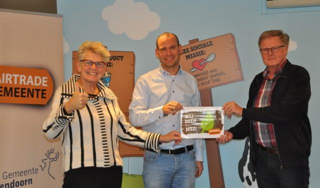 Directeur Tiemen Bloemberg van de ijsfabriek (midden) krijgt de sticker overhandigd door Willie Roskam en Gerrit van de Brink van Stichting Fairtrade Gemeente Hellendoorn.