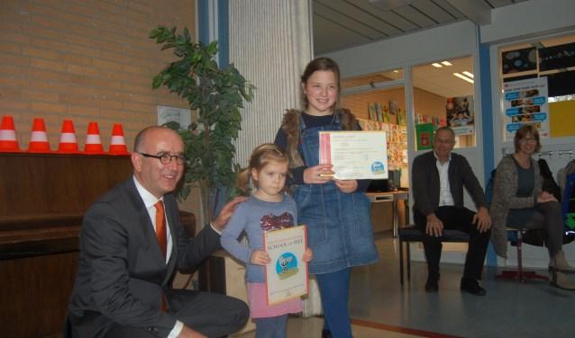 Wethouder Hoogland overhandigt het School op SEEF Veiligheidslabel aan de oudste en de jongste leerling van de Augustinusschool. (foto: Jacco van den Boogaart)