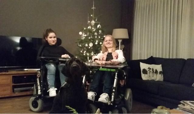 Meike van Mierlo (17) en Dena Huegen (20). Zij willen snel in aanmerking komen voor het medicijn Spinraza dat de kwaliteit van hun leven kan verbeteren. Maar men is het nog steeds niet met elkaar eens over de vergoeding. Op de voorgrond hulphond Oluk. Foto: Conny den Heijer