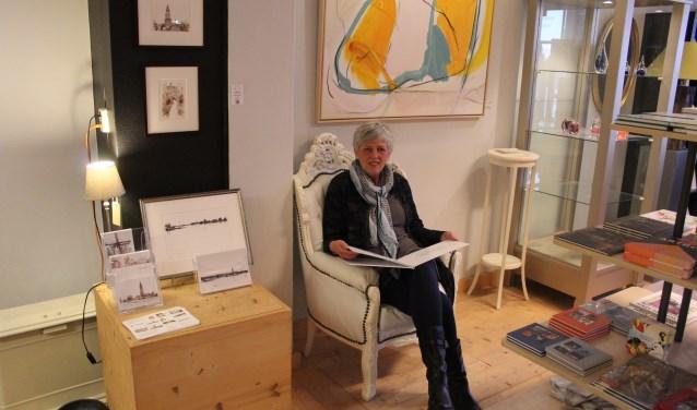 Margot Kikkert bij lijstenmakerij Ka-Art in de Herenstraat in Rhenen, daar waar onder meer haar recentelijk gemaakte  pentekeningen over Rhenen hangen. (Foto: Henk Jansen)