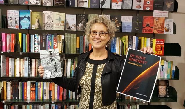 Bertina Mulder voor de boekenkast van boekhandel Kramer met haar debuutroman 'Wisselwerking' en de cover van 'De rode magneet'.