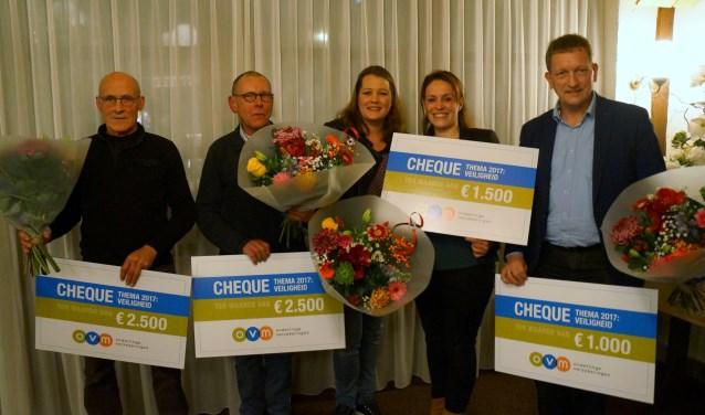 Vertegenwoordigers van enkele van de partijen die een donatie kregen, met de cheque en een bos bloemen.
