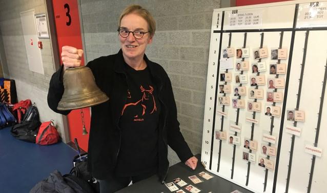 Marianne met de bel voor de volgende ronde, bij het afhangbord met de kaartjes die zij voor alle leden zelf fabriceert (Foto: Annemarie de Vries)
