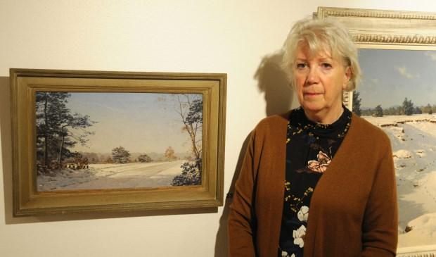 Diny Kinket bij het schilderij 'Noorderheide Laren' uit 1941. Rechts van haar is een deel van het grote sneeuwlandschap zichtbaar.