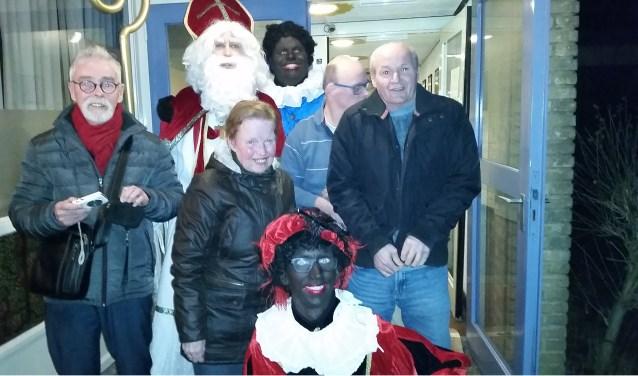 """Sint en zijn Pieten bezochten de soos in 'Ons Plekje' aan de Falckstraat in Vlissingen. Daar wilde hij nog graag even op de foto met enkele cliënten. Na afloop kreeg iedereen wat lekkers mee naar huis en verzuchtte de Sint: """"Het was weer een heerlijk avondje."""" Foto: Conny den Heijer"""