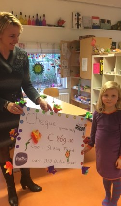 Jitty Wiggers (links), coördinator Stichting Present Deventer, terwijl ze de cheque met daarop het bedrag aangeboden krijgt van een van de kinderen van BSO Oudaen.