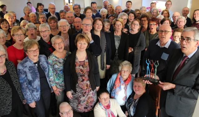 Samen 150 jaar: 100 jaar voor het koor en 50 jaar lidmaatschap van Kees Klein (tweede van rechts) naast voorzitter Beewukes met de sculptuur Applaus. FOTO: Lysette Verwegen