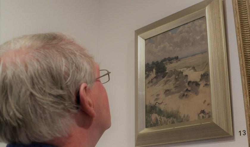 Een bezoeker van het museum bekijkt Duinlandschap op De Beer van Jan Voerman jr.  Foto Voerman Museum Hattem