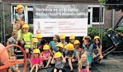 Een aantal leerlingen onthult het bouwbord tijdens een van de acties om de basisschool te behouden voor Noordeinde. foto: Batje van de Wetering