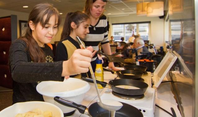 Stapels pannenkoek zijn er door leerlingen gebakken voor de ouderen in De Molenberg