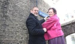 Wethouder Bob Duindam en historica Nettie Stoppelenburg schroeven bij het Spokepoortje het bordje van de Schoolsteeg stevig vast. (Foto: Gerard van Hooff)
