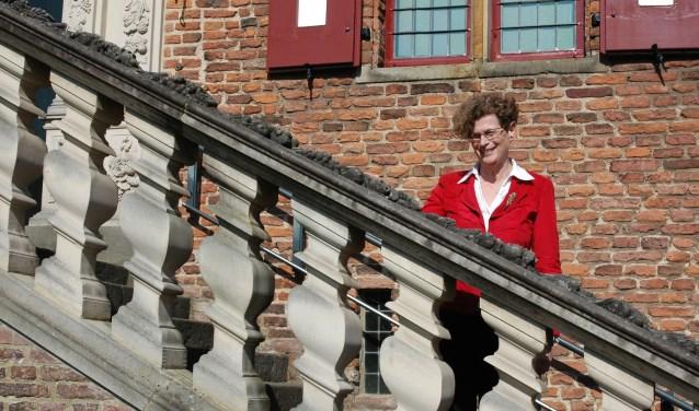 """Marijke Brouwer op de trappen voor het kasteel. """"Ik ben er trots op dat ik op zo'n bijzondere plek mag werken."""""""
