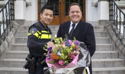 Brigadier Pufkus krijgt van burgemeester Van de Mortel een bos bloemen na zijn benoeming tot wijkagent.