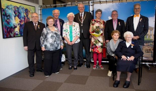 Mevrouw De Groot (zittend) met achter haar de overige gedecoreerden en de burgemeester.