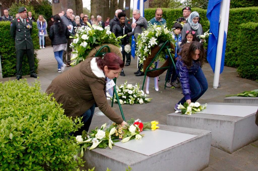 Nieuwe Nederlanders leggen bloemen bij het oorlogsmonument aan de Dijkstraat. Foto: Eveline Zuurbier