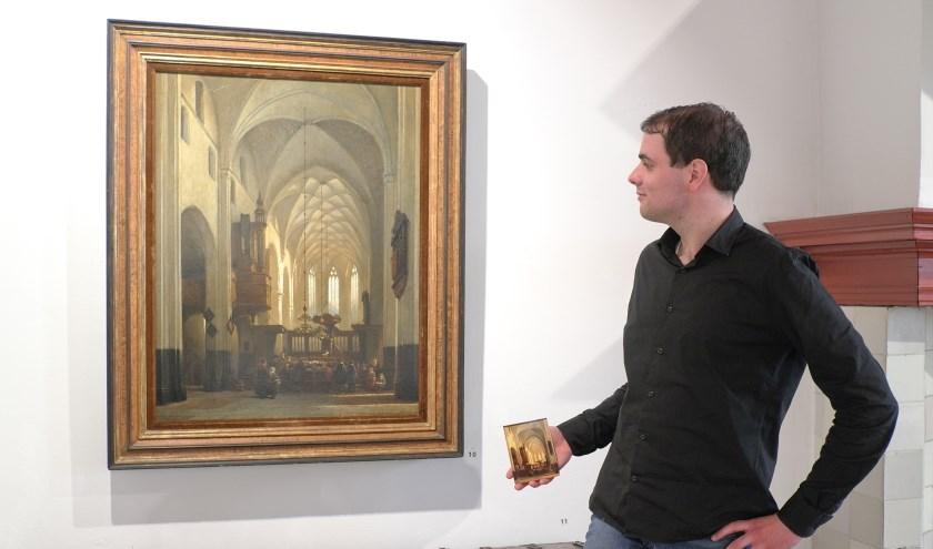 Kristian Kreeft bij het schilderij van Bosboom in het Voerman Museum Hattem. In zijn hand heeft hij een ansichtkaart waarop dit schilderij staat afgebeeld. Foto: Voerman Museum Hattem.