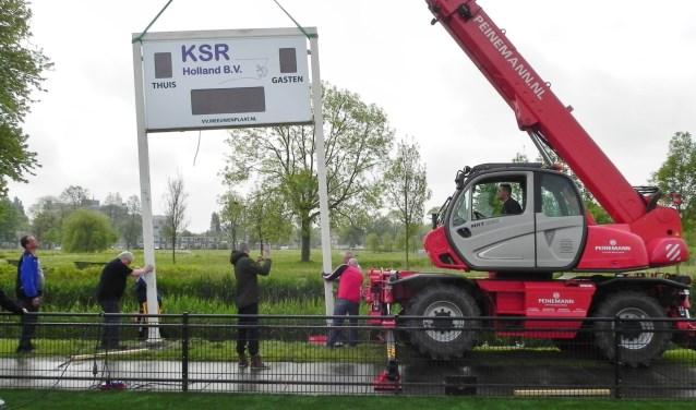 Een kraanwagen van Peinemann zet het nieuwe KSR scorebord op z'n plaats.