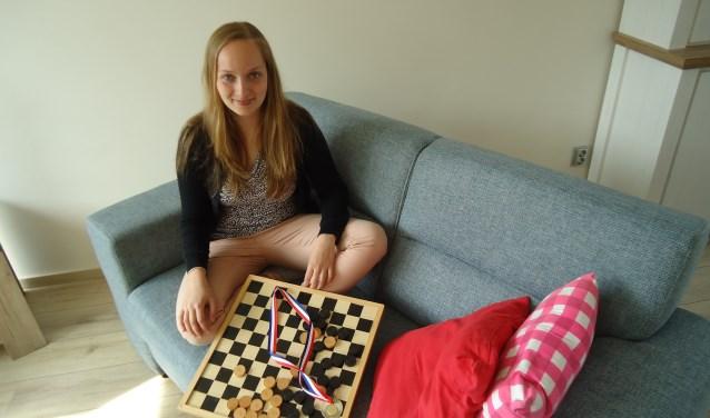 Dammen is de passie en verslaving van Laura Timmerman. ''Hoe meer je je erin verdiept, hoe leuker het wordt  Van het schaken ken ik de regels niet eens.'' (Foto: Nadia Tan)