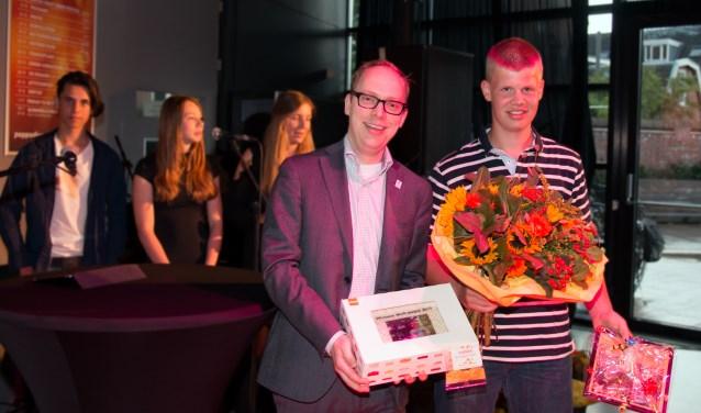 Huub Meijer (rechts) met de bloemen en de award. Links wethouder Eerenberg.