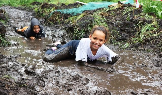 Kinderen tijgeren door de modder in Modderdorp in Park Waterland Spijkenisse. Foto: SKS Alles Kids