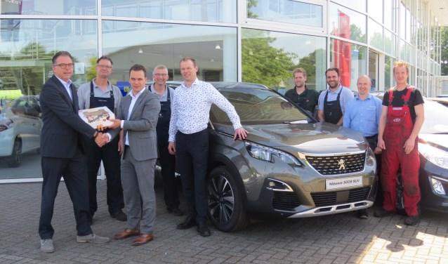 Joost Hooijmans (aftersales consultant Peugeot Nederland) overhandigt een taart aan Leon Schaddelee (clustermanager Peugeot Wassink Winterswijk). Foto PR