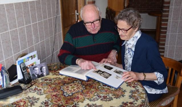 Tonnie Rijers en Toos Reijers-Van Druten bladeren door fotoboeken en halen oude herinneringen op. (Foto: Hanneke Hoefnagel)
