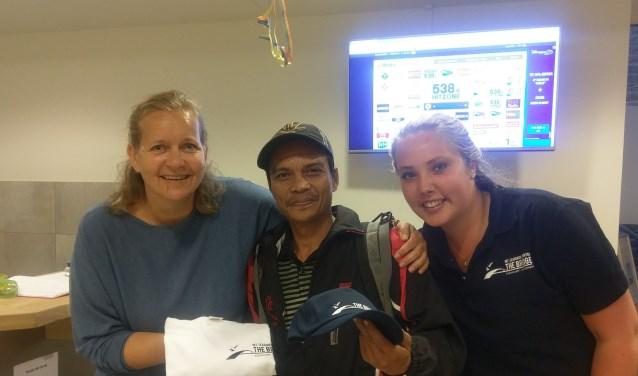 Vrijwilligers Anushka Nooteboom (links) en Danique Jennissen verrassen de 1500e bezoeker met een T-shirt en een cap van Zeemanshuis The Bridge.