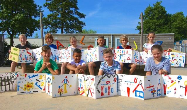 Kinderen van de Abacus poseren met kunstwerken die door groep 5 zijn gemaakt. (Foto: Kirsten den Boef)